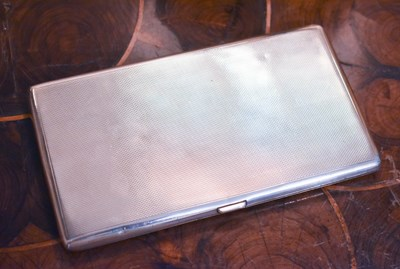 Lot 13 - A silver cigarette case, machine engraved and...